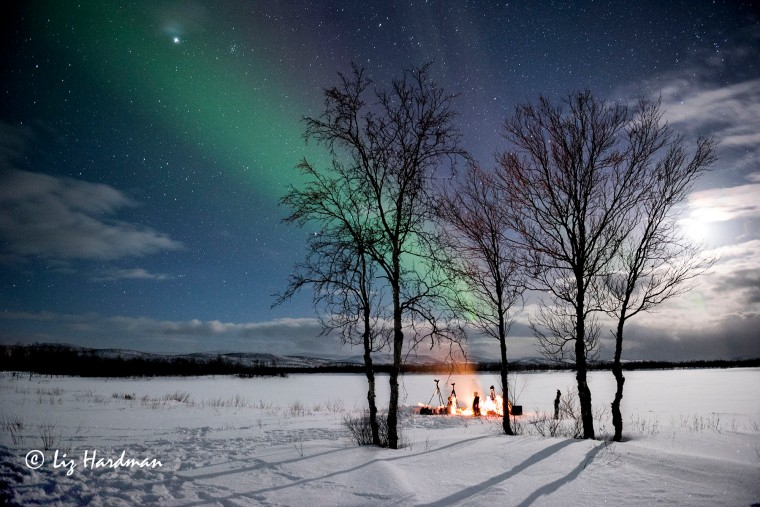 A campfire under a moonlit sky with the dancing Northern Lights. It was extraordinary experience sitting out in the snowy expanse at -14*C.
